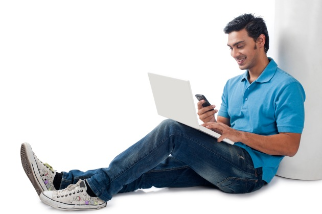 Bengali man using a laptop and text messaging on a mobile phone