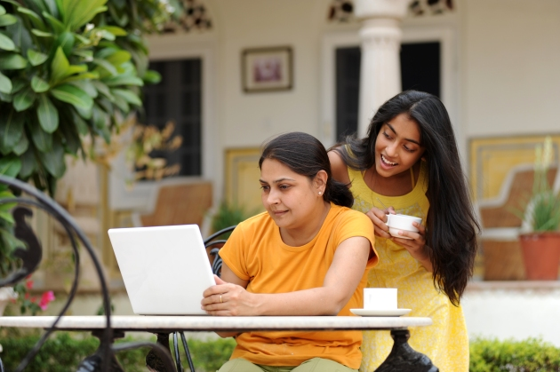 Loving mother and daughter with laptop in outdoors